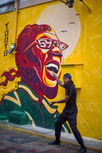 Picture of man standing in front of a mural painted by Joshua Solas