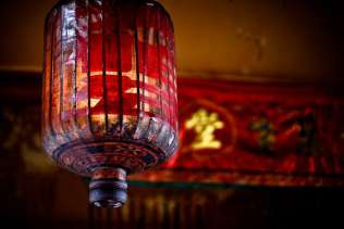 Chinese lantern hangs in the temple in Penang. In ancient and traditional red Chinese lantern hangs in the temple in Penang, Malaysia. These old bamboo and paper lanterns are becoming less and less used as the makers of the lanterns are disappearing.