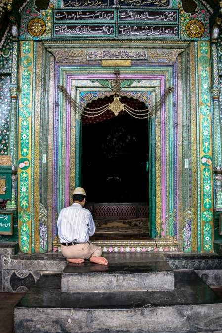 A Kashmiri man prays at the entrance to The shrine of Mir Syed Ali Hamadani.