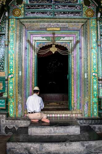 A Kashmiri man prays at the entrance to The shrine of Mir Syed Ali Hamadani.