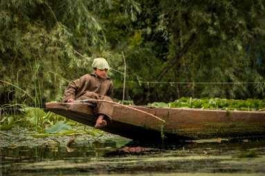 A young boy fishing on Dal Lake, Srinagar.