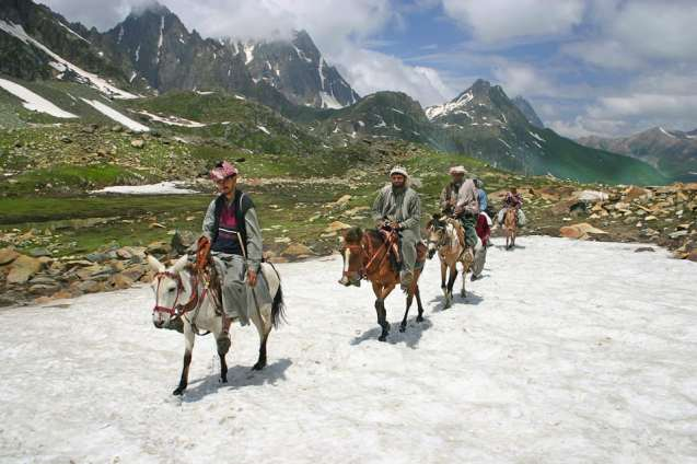 Bakarwal Gujjars riding through a mountain pass.