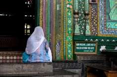 A Kashmiri woman prays at the entrance to The shrine of Mir Syed Ali Hamadani.