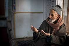 A Pir (holy man) prays to a dead saint at Makhdoom Sahib Shrine,