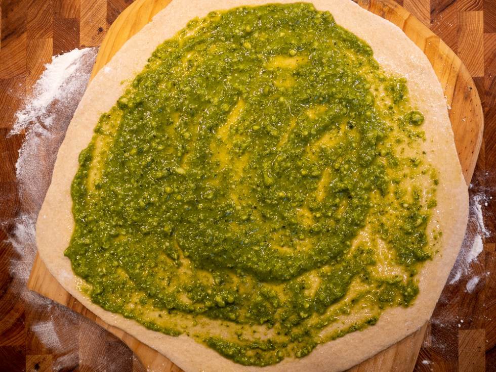 The unbaked pizza topped with pesto sauce.