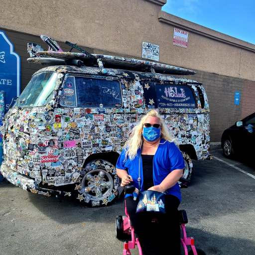 The Disabled Diva is a 50 something white woman with long curly blonde hair sitting on a pink power foldable wheelchair in front of a VW van that is covered with stickers in San Diego