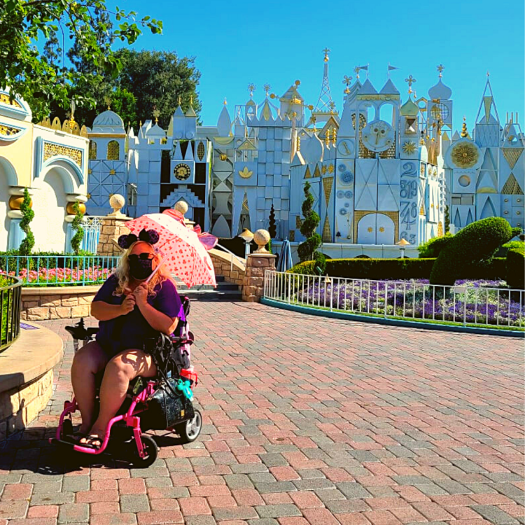 The Disabled Diva in front of Small World at Disneyland