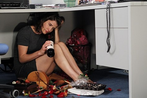 Sad woman sitting under a desk with a wine bottle.