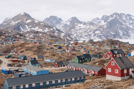 The town of Tasiilaq in southeastern Greenland with snow covered mountains in the background.