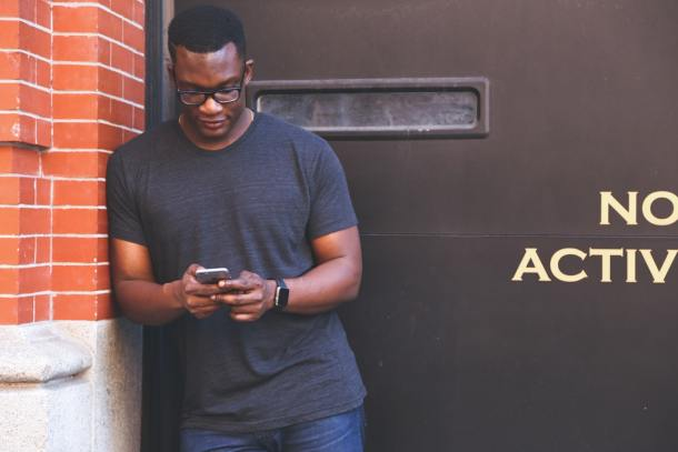 black male researching prostate cancer on his mobile phone