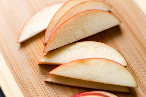 Sliced apples resting on a bamboo cutting board