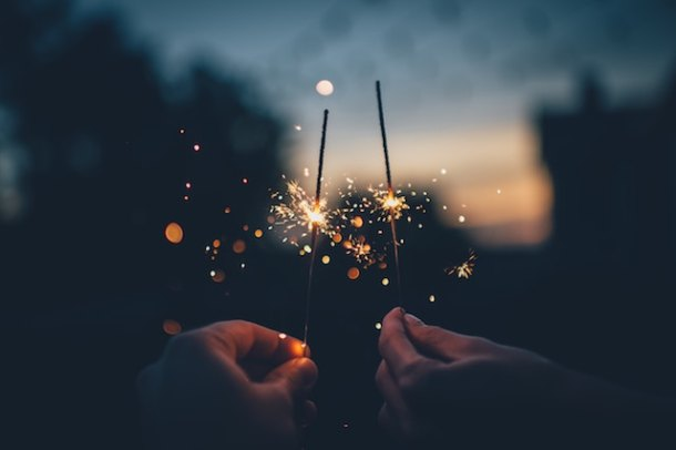 People holding sparklers at night