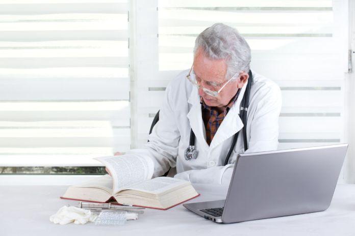 older doctor w: book & computer (123RF)