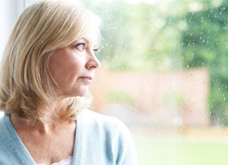 Sad Mature Woman Suffering Looking Out Of Window 1687 x 1126