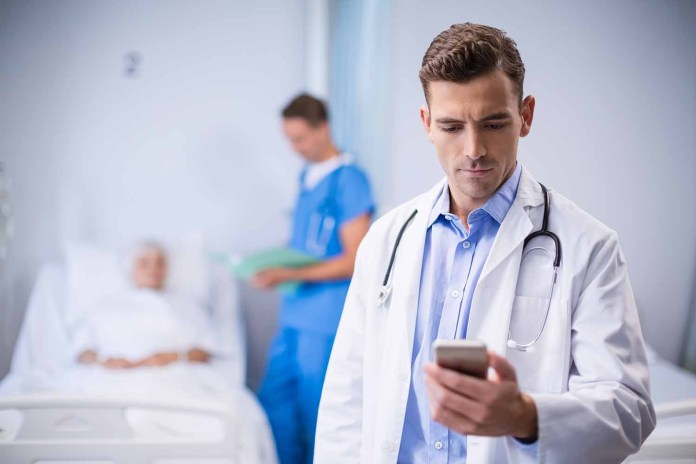 Doctor on ward using cell phone 1500 x 1000