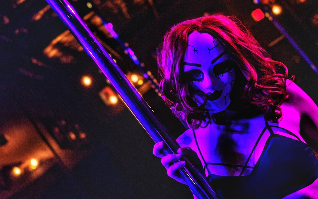 Pole dancer in creepy doll mask
