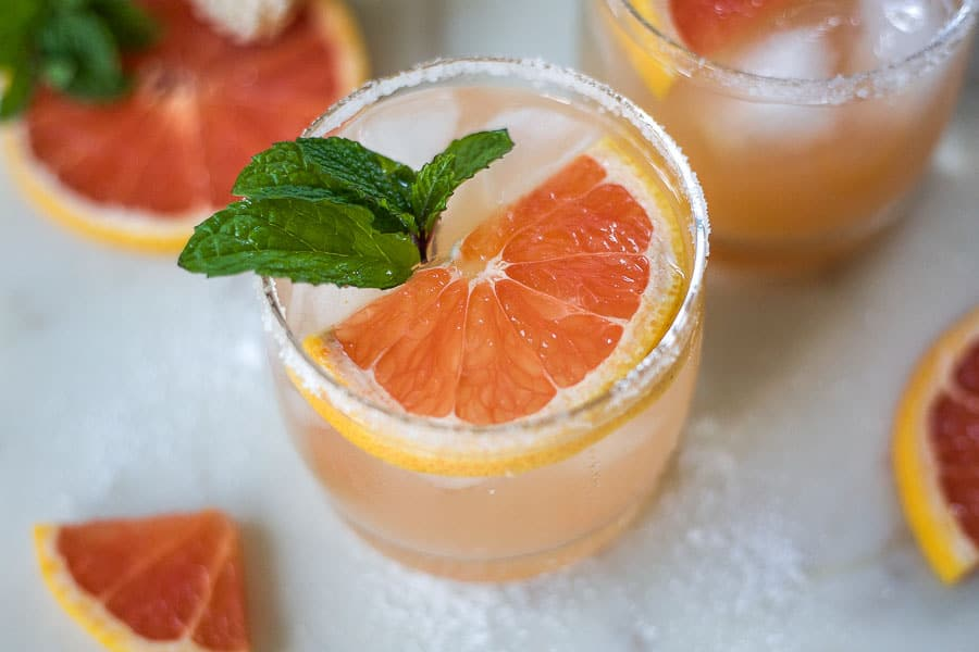 salty dog cocktail featuring glass with fresh grapefruit, mint and vodka