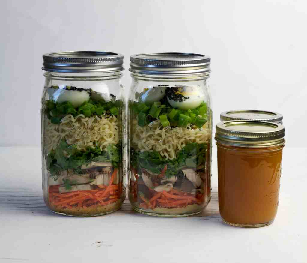 ramen soup ingredients in two mason jars with broth in two smaller jars