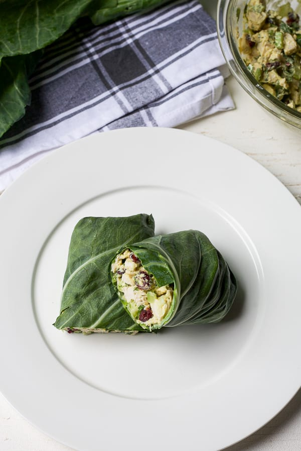 2 halves of a collard green wraps with chicken salad in background