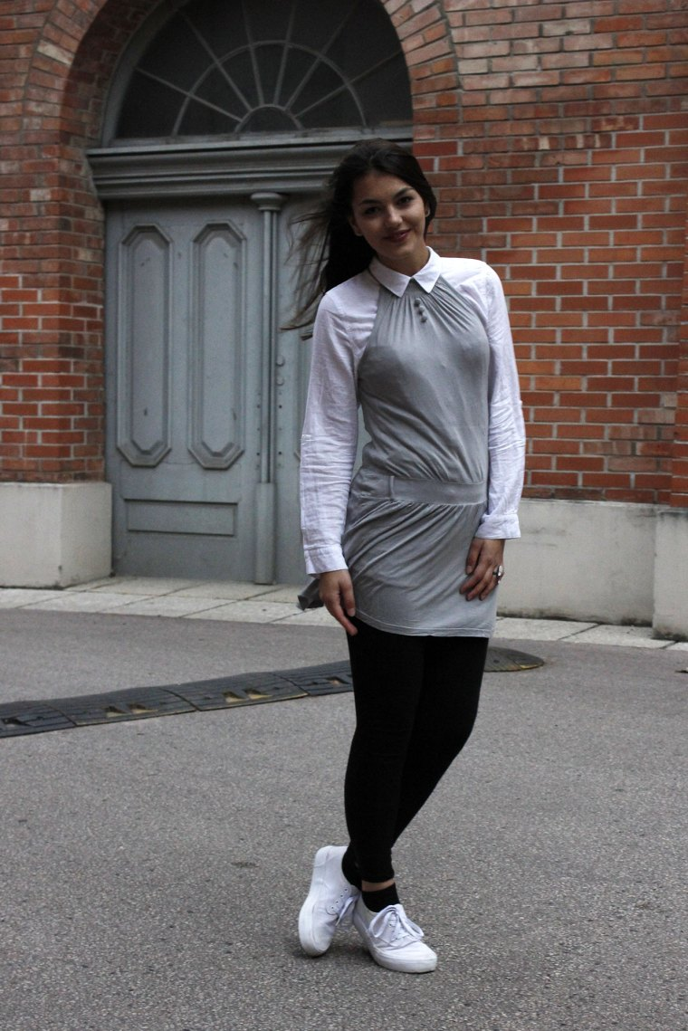 Dorie wearing a grey dress and a white blouse with black legging and white shoes