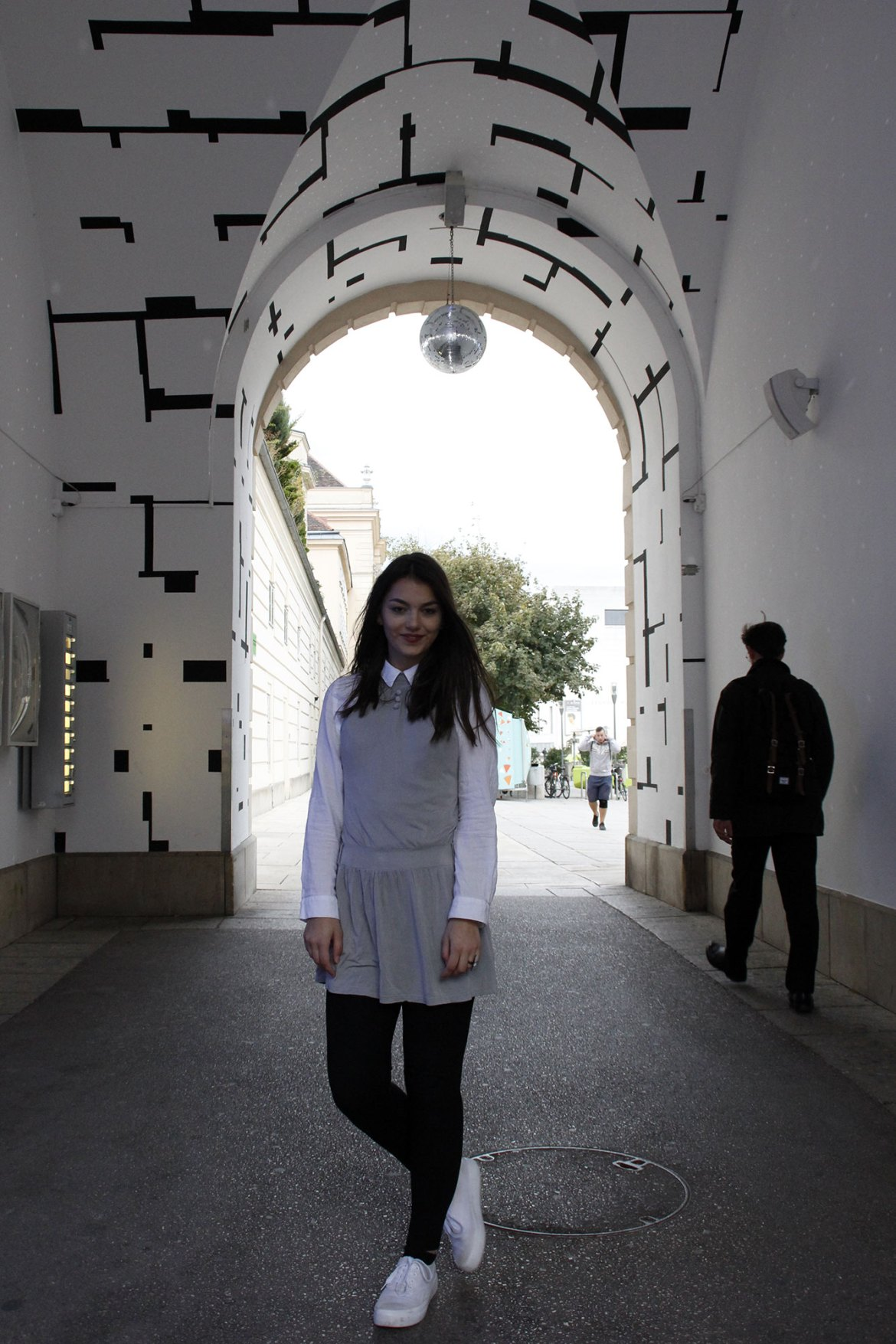 Dorie standing in a black white tunnel, waring a grey dress, a white blouse, black legging and white shoes