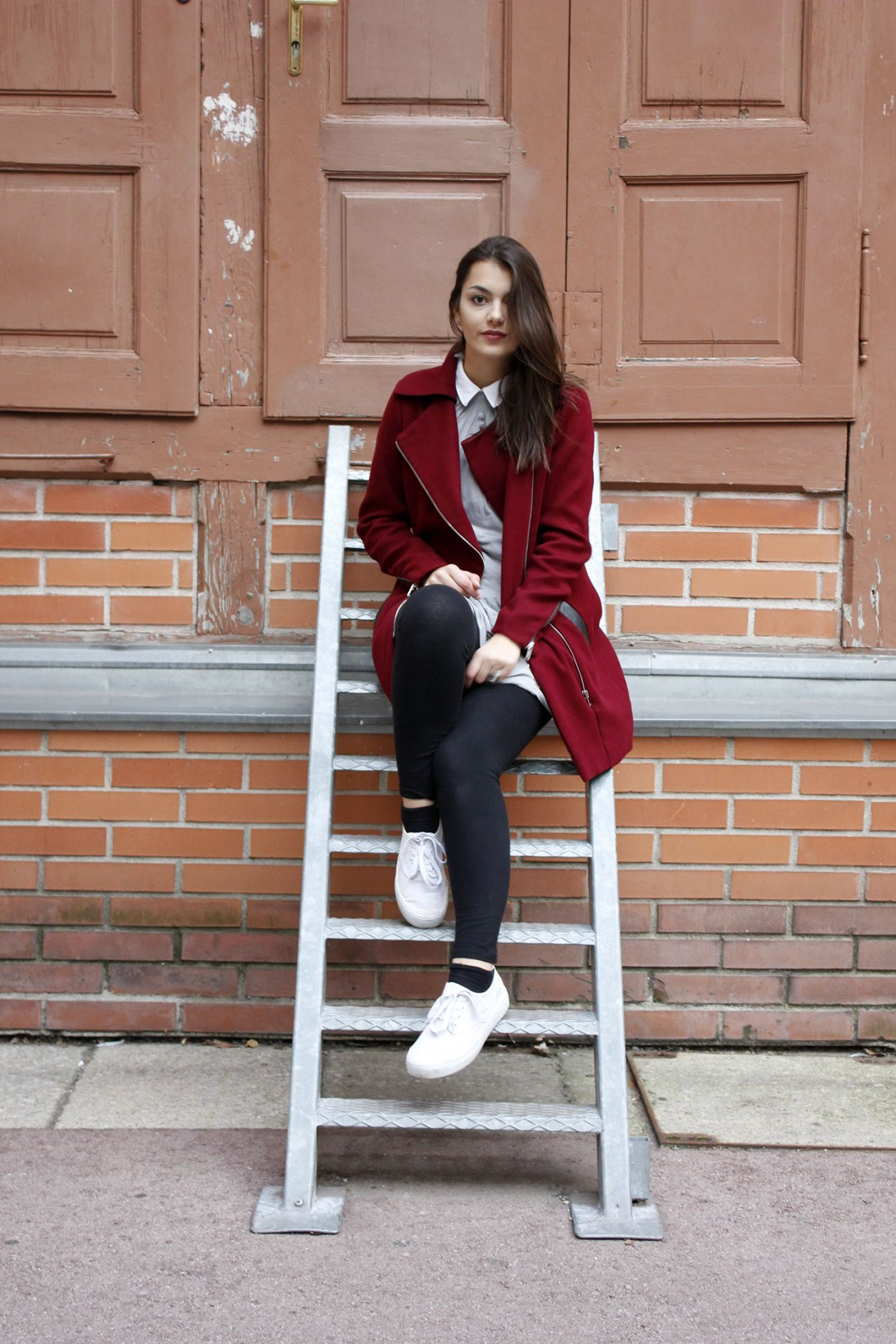 Dorie sitting on a ladder, wearing a red coat from Stradivarius, a grey dress, black legging and white shoes from even&odd