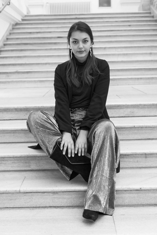 Dorie trägt ihr Silvester Outfit mit silberner Hose von Mango und sitzt auf einer Treppe mit Clutch in der Hand