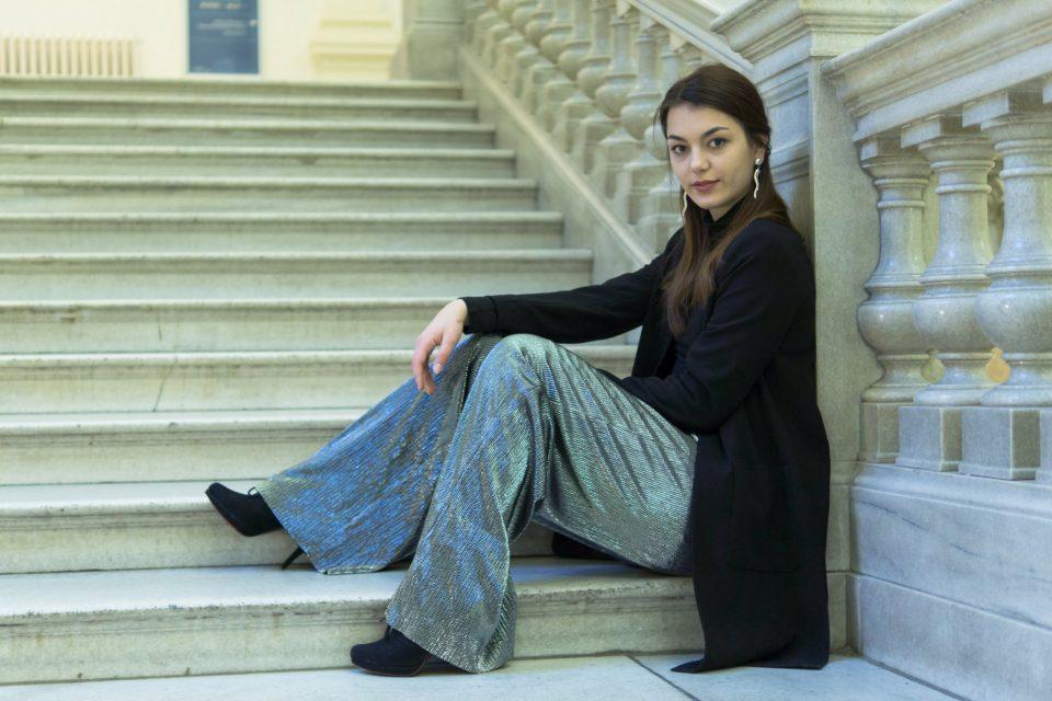 Dorie sitzt auf einer Treppe und trägt ein Silvester Outfit mit silberner Hose von Mango