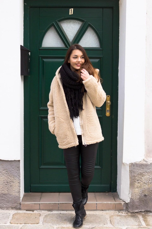 Dorie trägt eine Teddy Jacke, steht in vor einer grünen Tür und lacht