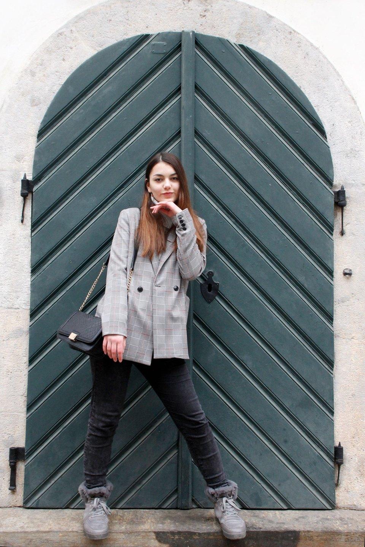 Dorie trägt einen grau-karierten Blazer von Pull & Bear mit einem Strickpullover und dunklen Jeans