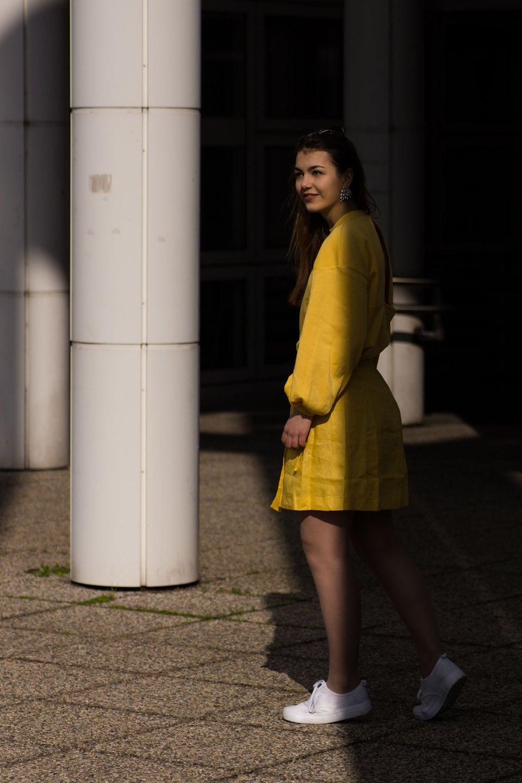 Dorie im gelben All-Over-Look im Halbschatten