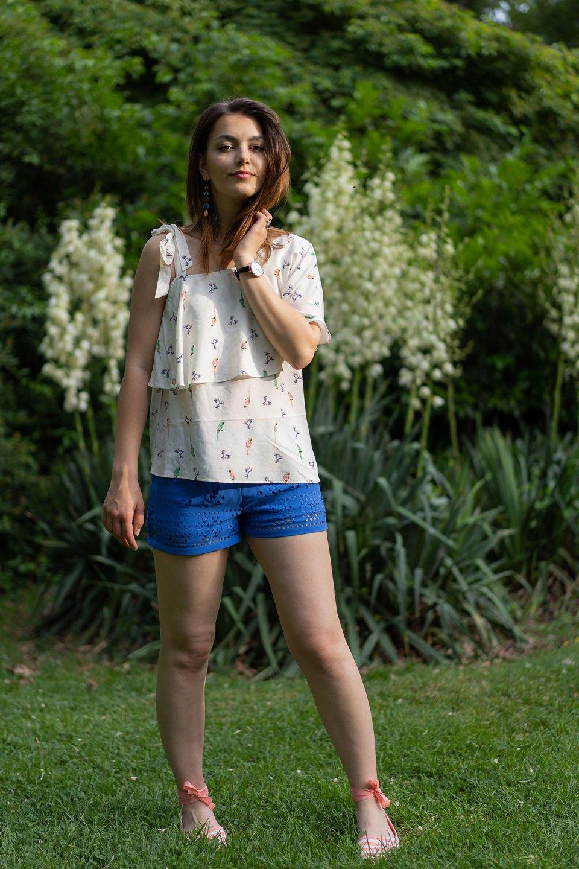 Dorie trägt ein verspieltes Outfit mit Papageien-Print Oberteil von Espirt, blauer Hose und Espanrilles