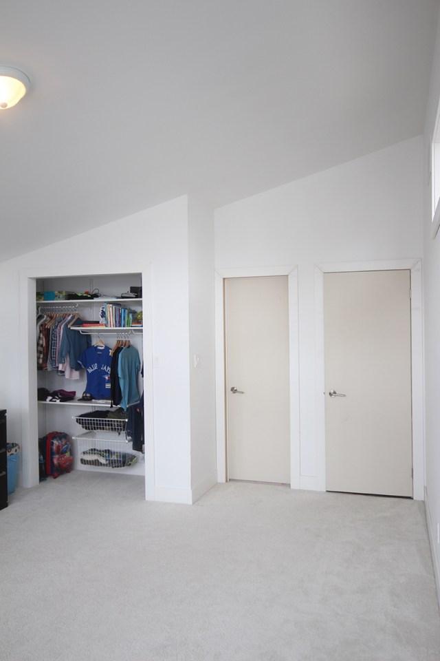 Boys bedroom before: primed hardboard slab doors mark the entrances to the room and en-suite.