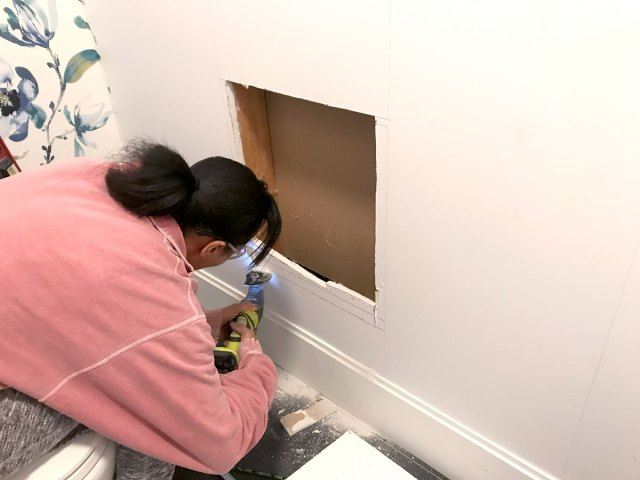 Cutting out the drywall to create a niche inset between studs that will hold magazines and the toilet paper holder