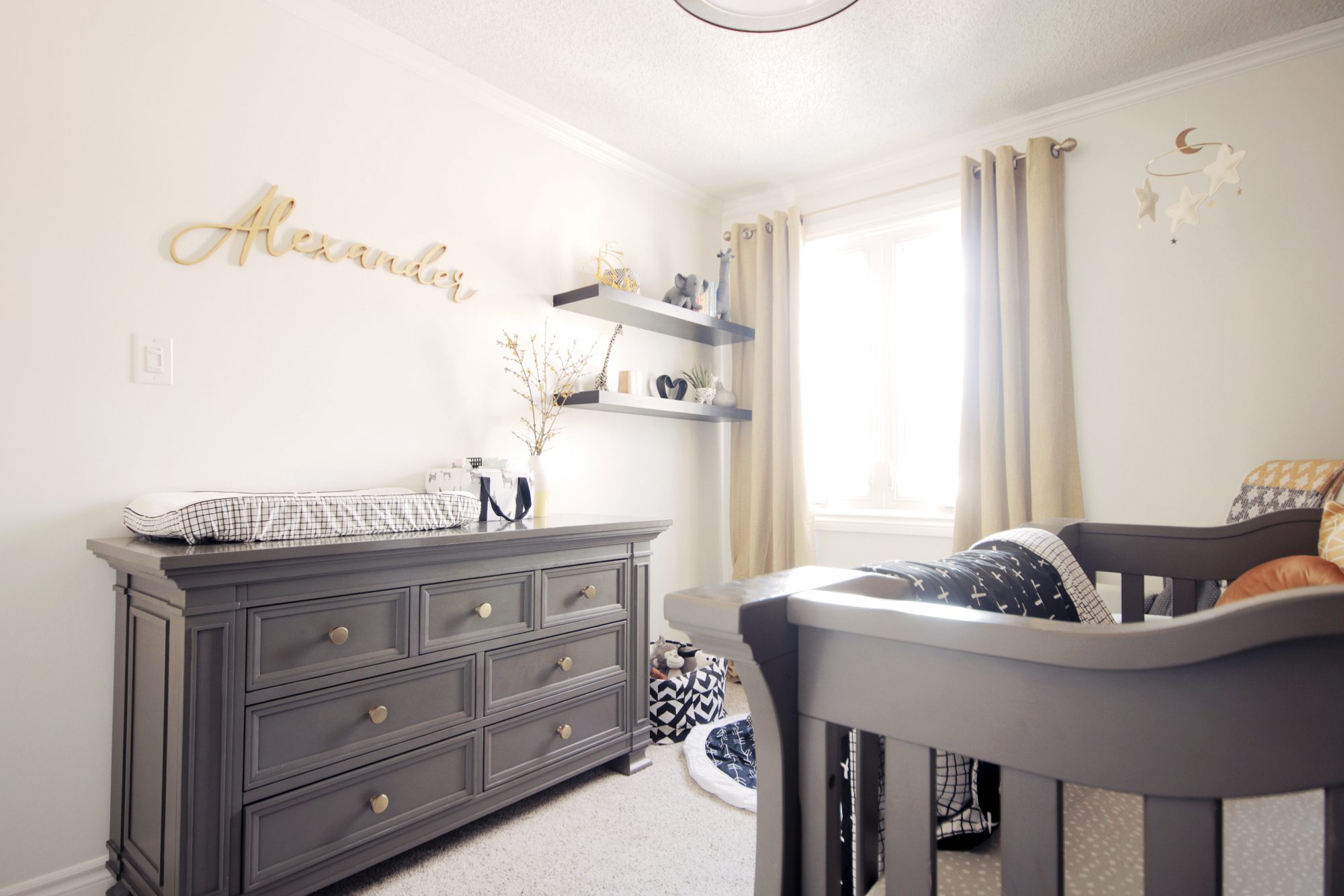 Warm white walls and golden accents keep the nursery feeling light and airy
