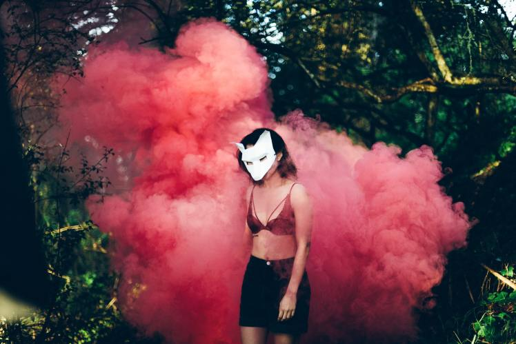 Woman with white wolf mask in red fog for the meaning of becoming a wolf in a dream
