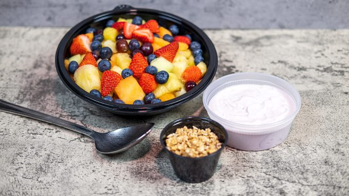 Fresh Fruit with Yogurt and Granola positioned on a concrete backdrop with a metal serving spoon.