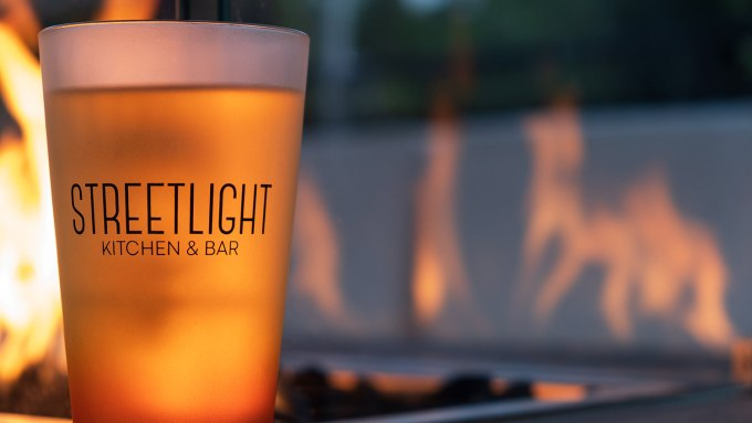 The 16oz pint glass with the Streetlight Kitchen and bar logo on it photographed in front of a firepit outdoors. The glass is 7/8ths filled with an amber colored liquid.