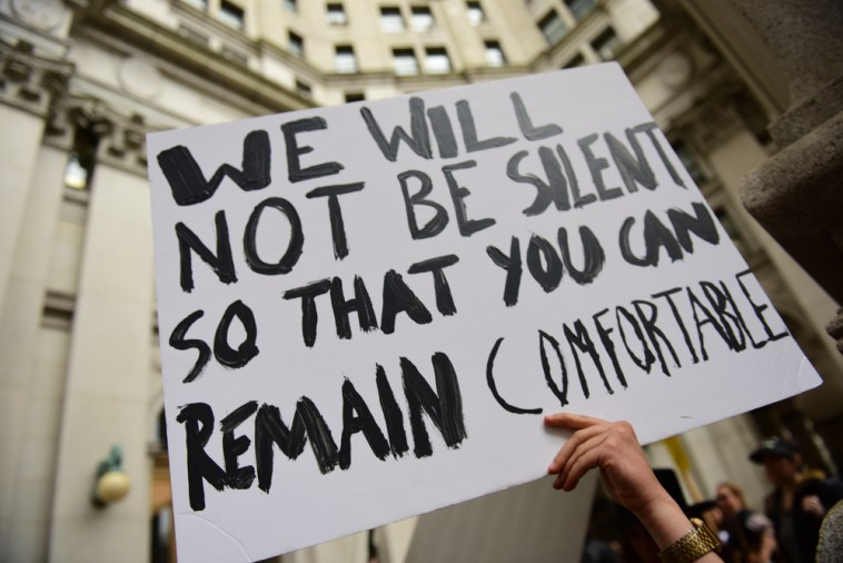 A protestor holds us up a fundamental part of what defines the freedom of speech. Source: theduran.com