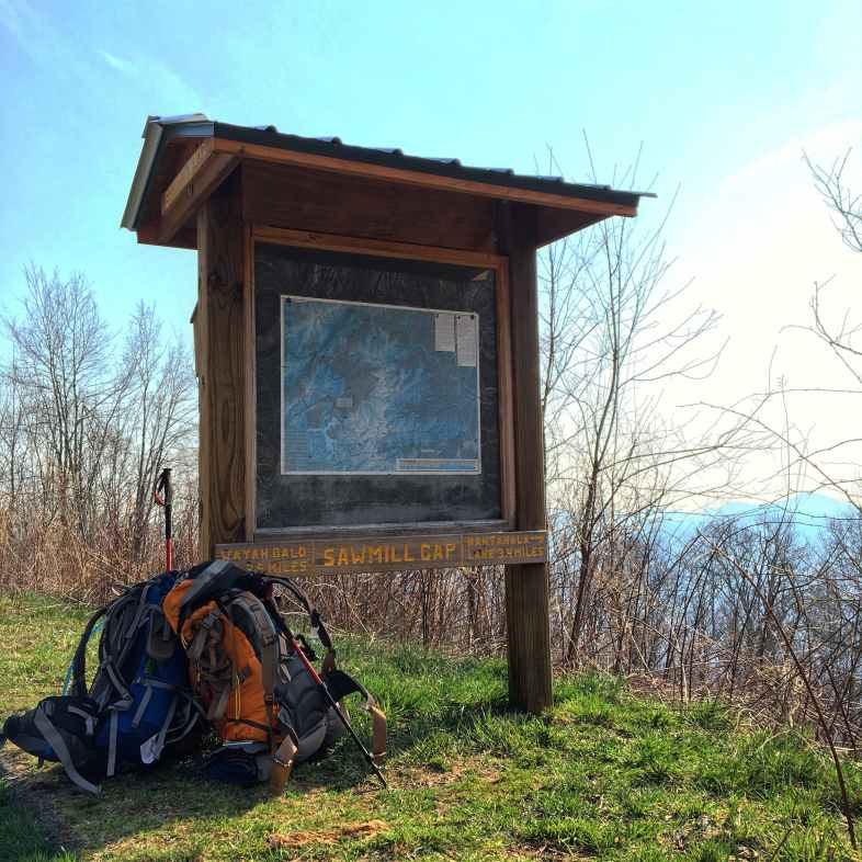 a pair of loaded backpacks rest under an informational sign on a hiking trail