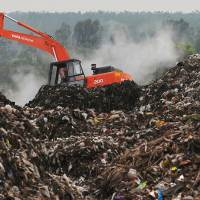 Digger on top of landfill with UK Fast Fashion Waste