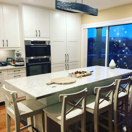 The original floors really shine with all white cabinetry and new pot lighting. The perfect DVI shaded pendant was a find from The Lampost in Kamloops and mirrors the shape of the matte black cabinet pulls
