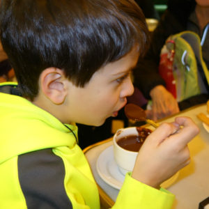 boy eating churros and hot chocolate in madrid at san gines chocolateria