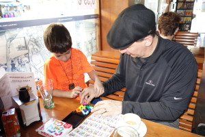 father and son playing a game at a cafe, Traveling with Kids: Top Tips, www.theeducationaltourist.com