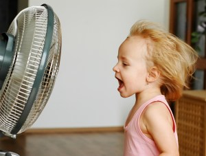 No air conditioning child singing in front of fan