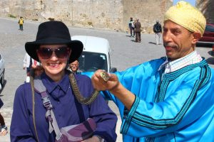 Snake charming - The Educational Tourist with snake on shoulder
