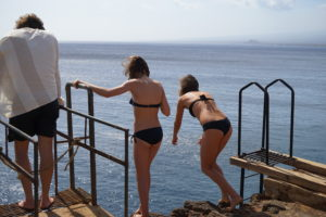 girls jumping off cliff South Point, Hawaii, www.theeducationaltourist.com