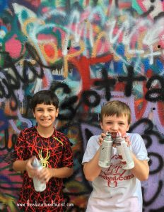 boys with spray cans in front of spray painted walls, Hope Outdoor Gallery, www.theeducationaltourist.com