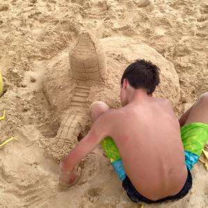 boy building sand castles at Aulani Disney resort in Hawaii