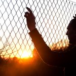 silhouette-man-behind-fence